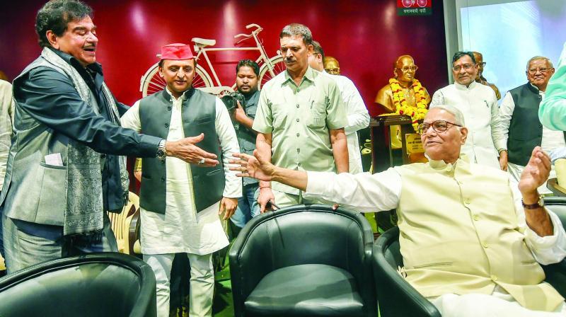 BJP MP Shatrughan Sinha shakes hands with former BJP leader Yashwant Sinha as SP president Akhilesh Yadav looks on in Lucknow on Thursday. (Photo: PTI)