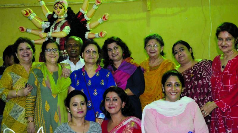 Women of the Durga Bari Samiti posing before giving final touches to the idol.