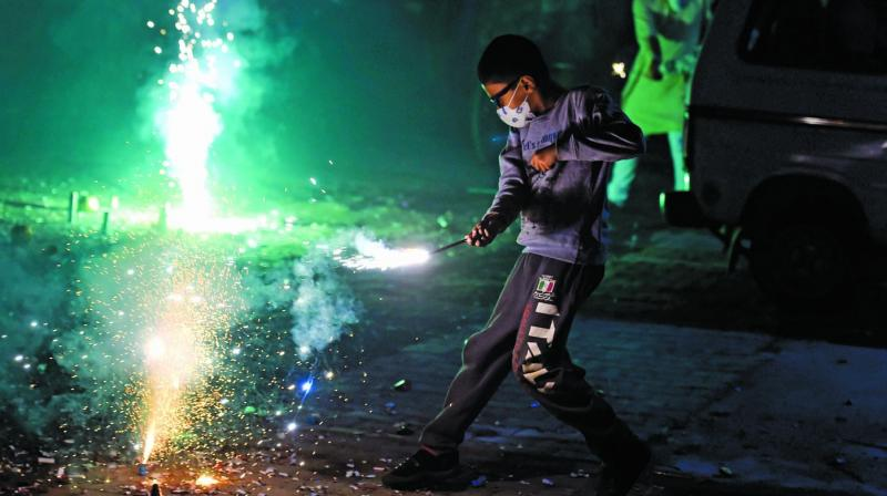 A boy (above), wearing a pollution mask, burns crackers during Diwali celebrations in New Delhi on Wednesday. (Photo: PTI)