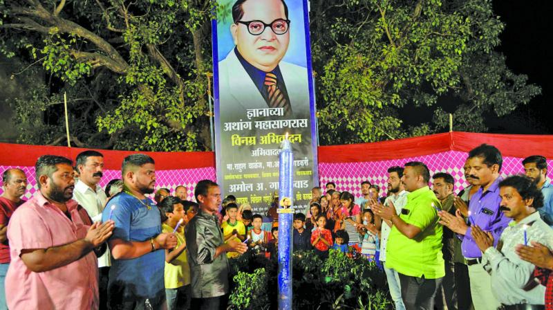 Residents of Siddharth Nagar pay tribute to Bharat Ratna Dr Babasaheb Ambedkar by lighting a six-foot-tall candle to mark his 62nd death anniversary at Chembur on Wednesday in Mumbai. (Photo: Rajesh Jadhav)