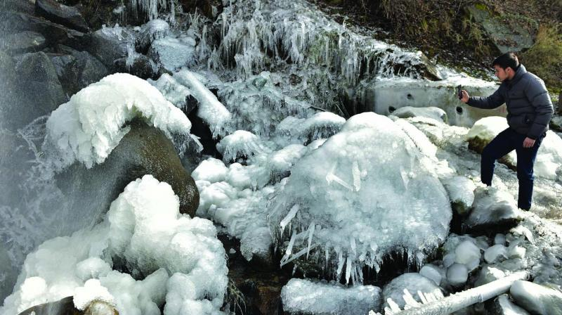 A tourist takes photos of icicles formed after snowfall at Pahalgam in Anantnag district of south Kashmir.
