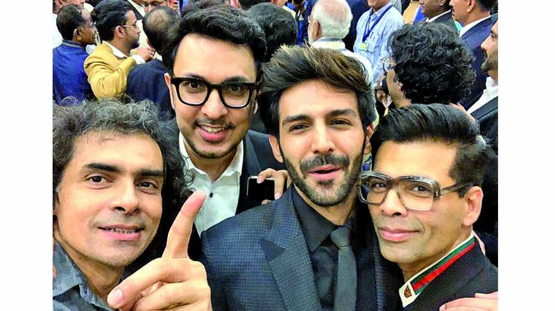 Imitiaz Ali who couldn't get a selfie with PM Narendra Modi struck a pose with Kartik Aaryan, Karan Johar with PM Narendra Modi in the background.