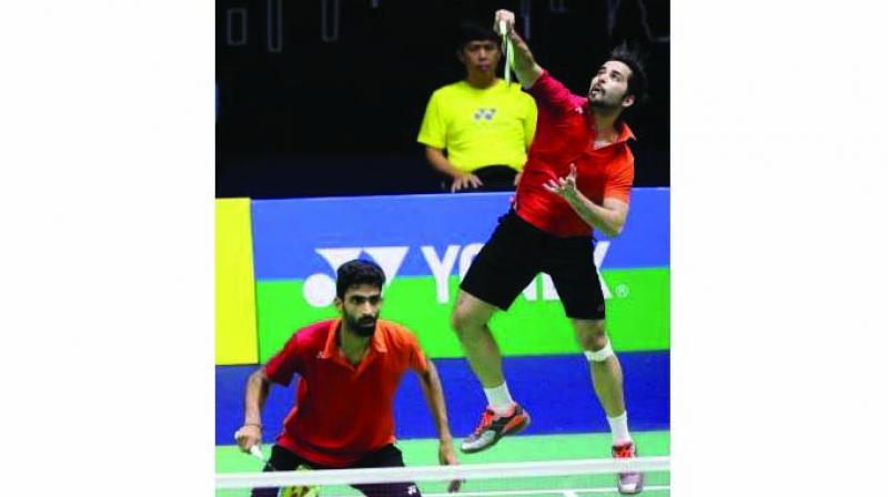 Manu Attri plays a shot as partner Sumeeth Reddy stays alert during their men's doubles match against Mads Pieler Kolding and Niclas Nohr of Denmark at the Indonesia Masters on Wednesday.