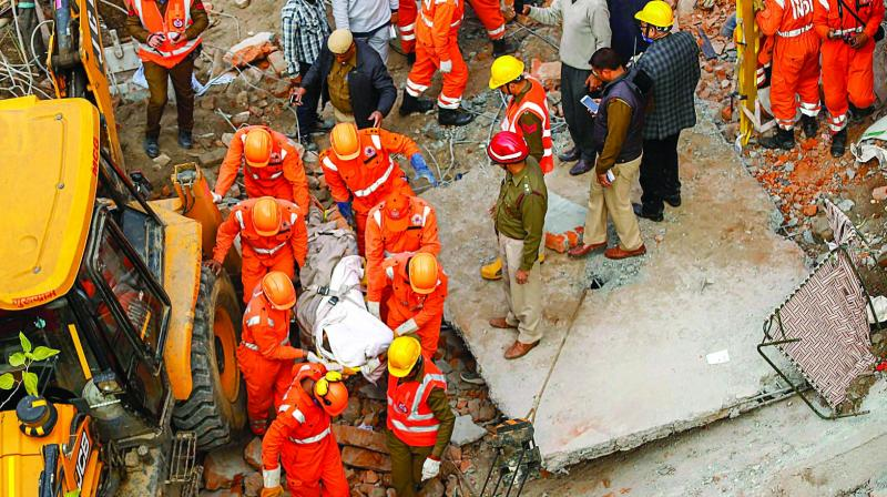 Rescue workers recover a body from the debris after a four-storey building collapsed in Gurgaon early on Thursday morning. (Photo: PTI)
