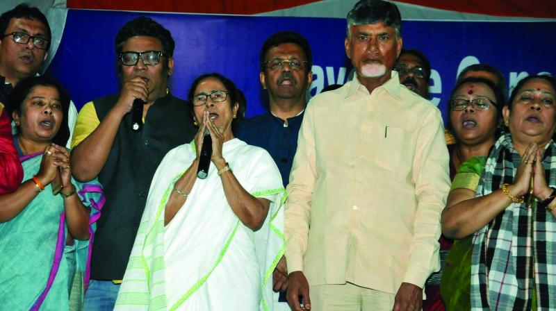 West Bengal chief minister Mamata Banerjee with TDP chief and Andhra Pradesh chief minister N. Chandrababu Naidu stand for the national anthem after announcing the end of her 46-hour-long dharna in Kolkata on Tuesday. (Photo: PTI)