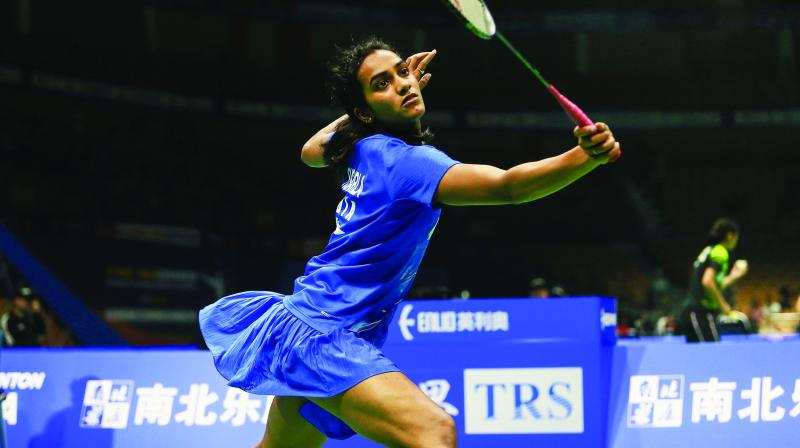 P. V. Sindhu hits a return against Sayaka Takahashi of Japan during their womens singles first round match at the Badminton Asia Championships in Wuhan, China, on Wednesday. Sindhu won 21-14, 21-7. (Photo:  AFP)