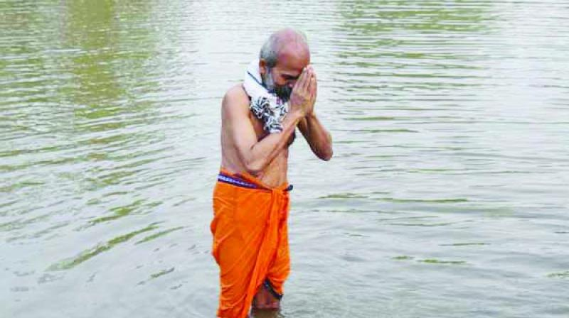 Pratap Sarangi taking bath in his village pond on Sunday.