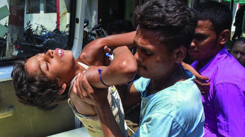 A child showing symptoms of  Acute Encephalitis Syndrome being shifted to a hospital in Muzaffarpur on Tuesday. At least a dozen children in the city have died due to the disease while many others are being treated in several hospitals. (Photo: PTI)
