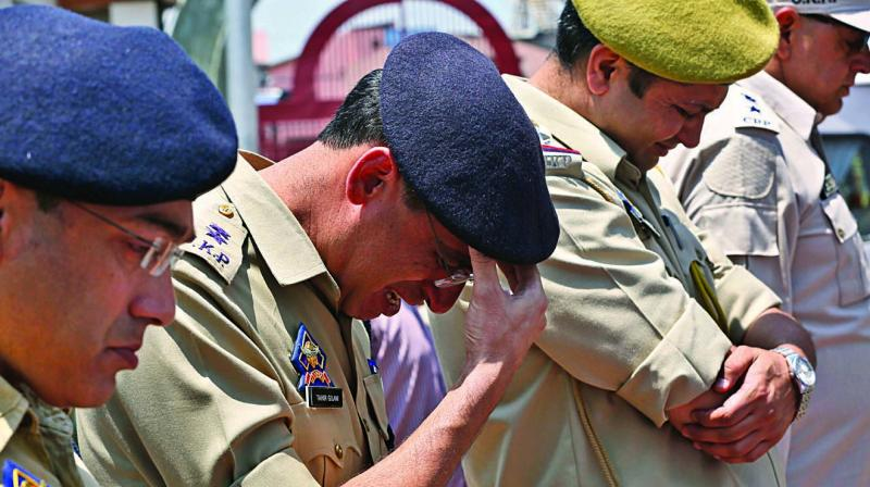 A police officer weeps near the coffin of colleague Arsheed Ahmad as he pays homage to Ahmad during a wreath laying ceremony in Srinagar on Monday. Police inspector Ahmad, who was critically injured in a militant attack in J&K's Anantnag district on June 12, had succumbed to his injuries on Sunday afternoon at the All India Institute of Medical Sciences in New Delhi.(Photo: AP)