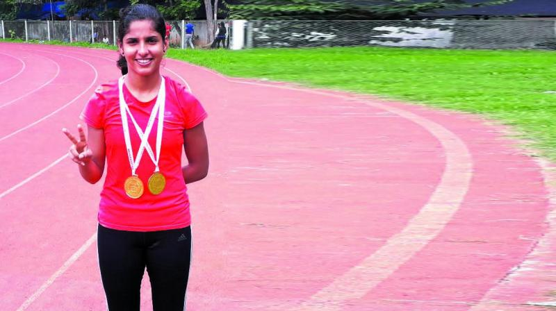 Nidhi Singh of Thane is all smiles as she poses with her medals.