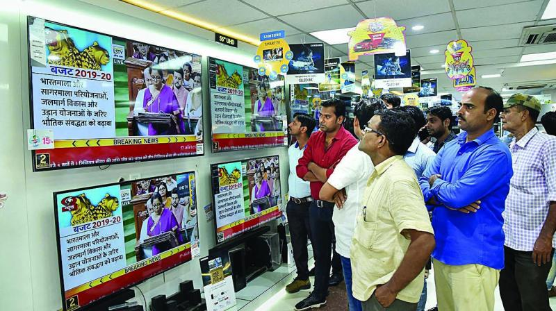 People watch finance minister Nirmala Sitharaman tabling the Union Budget 2019-20 on TV sets at a showroom in Patna on Friday. (Photo: PTI)