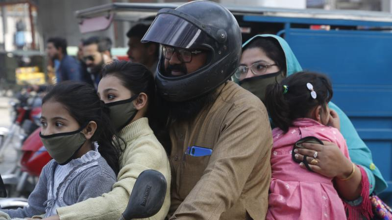 A Pakistani family wears face masks to help prevent exposure to the new coronavirus as they travel on a motorbike in Lahore, Pakistan. AP Photo