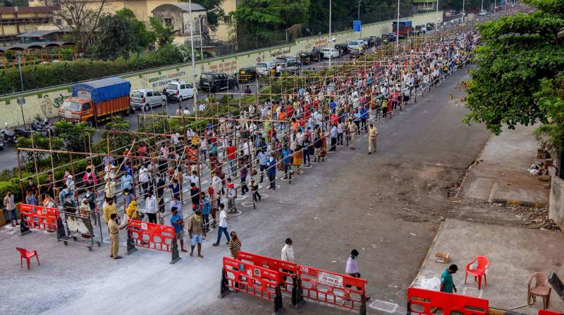 People stand in queues to enter APMC Vegetable Market, during a nationwide lockdown, imposed in the wake of coronavirus pandemic in Navi Mumbai. PTI photo