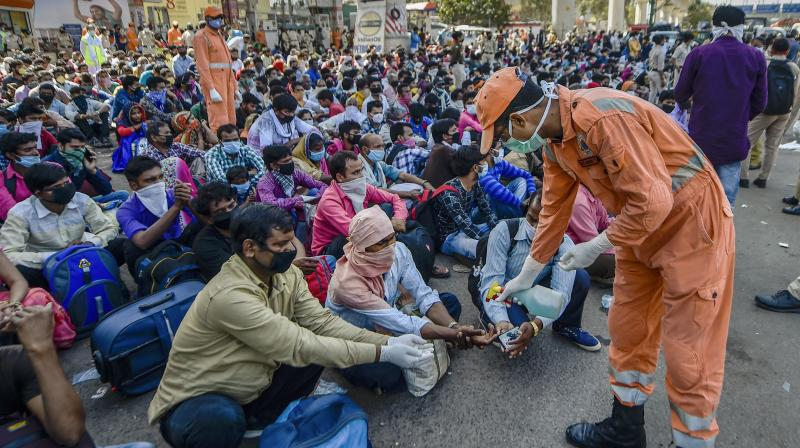 A National Disaster Response Force (NDRF) offical sprays santizers on the hands of migrants, who have been walking to their respective villages amid a nationwide lockdown in the wake of coronavirus pandemic, near Delhi-UP Border in New Delhi. PTI photo
