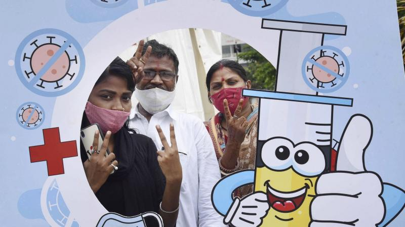 Beneficiaries pose for photographs after receiving a dose of the COVID-19 vaccine at a 24 hours vaccination center in Patliputra Sports Complex in Patna. (Photo: PTI)