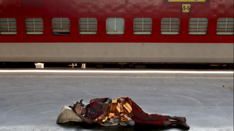 A homeless woman sleeps on a deserted platform of a Lokmanya Tilak train terminus in Mumbai, March 23, 2020. As India expanded its virus-containment measures and halted its lifeblood train network, the federal government warned Monday of strict legal action for those who flout the rules. (AP)