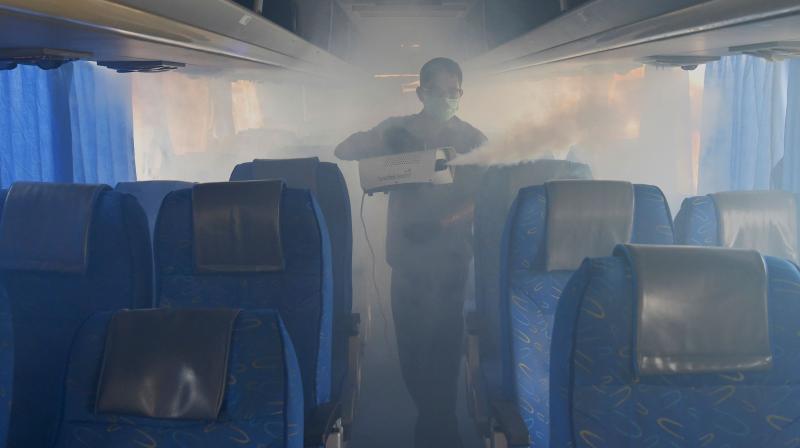 A worker disinfects a Karnataka public transport bus to contain the coronavirus. (PRI)