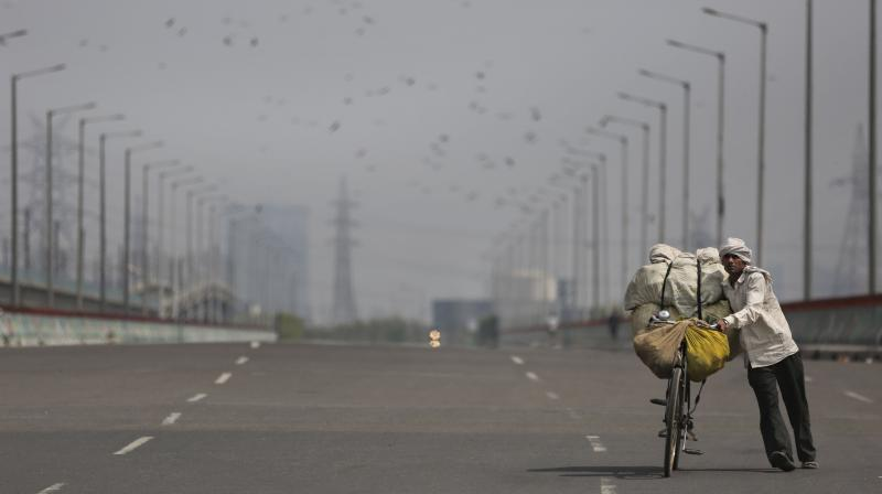 A vegetable vendor pushes his bicycle loaded with vegetables on an empty street during a complete lockdown amid growing concerns of coronavirus in Noida, on the outskirts of New Delhi on March 24, 2020. Authorities have gradually started to shutdown much of the country to contain the outbreak. (AP)