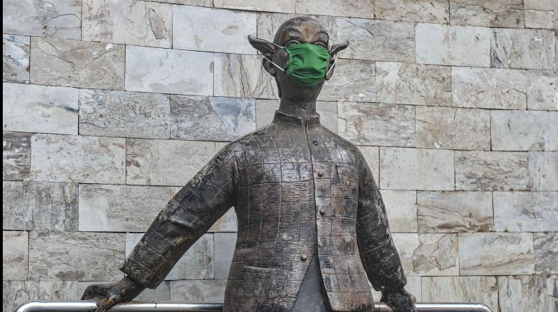 A statue of the Common Man, made famous by the cartoonist R K Laxman, is seen wearing a protective mask in Mumbai on March 23, 2020. (PTI)
