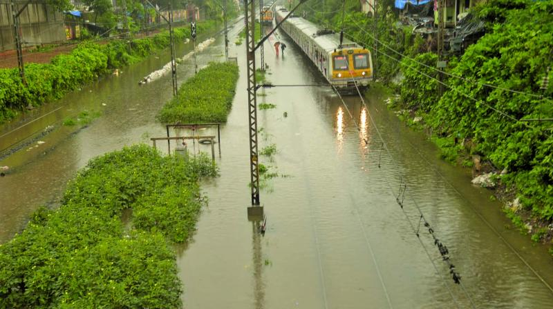 Local train wades through flooded railway tracks after a heavy rainfall in Sion on Wednesday. (Photo: RAJESH JADHAV)