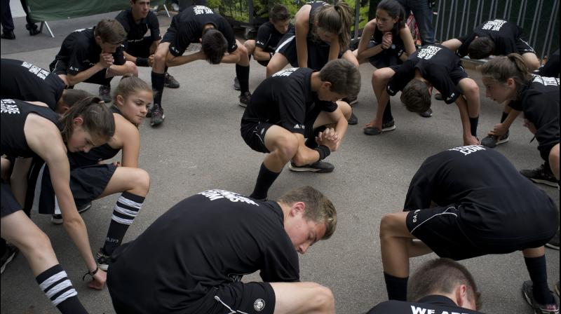 HANDS IN GLOVES: Ball-boys and girls do stretching exercises at the Roland Garros stadium, in Paris. AP Photo