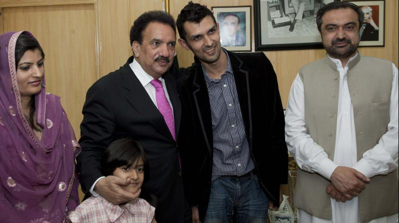 Pakistani Interior Minister Rehman Malik (2L) with former Pakistan wicket-keeper Zulqarnain Haider (C) and his family members in Islamabad after the cricketer's return home from England. Pakistan Sports Minister Shaukat Ullah looks on. AFP Photo