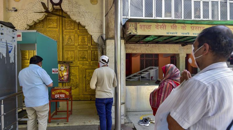 Devotees offer prayers outside Hanuman temple in Connaught Place, during the ongoing COVID-19 nationwide lockdown, in New Delhi. PTI photo