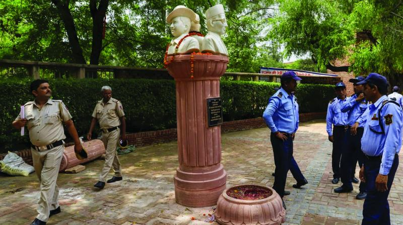 Policemen and security personnel stand guard around the busts of Veer Savarkar, Subhash Chandra Bose and Bhagat Singh in Delhi University on Thursday. (Photo: PTI)