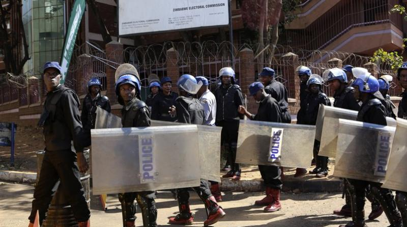 Police patrol outside the Zimbabwe Electoral Commission offices in Harare. (Photo: AP)