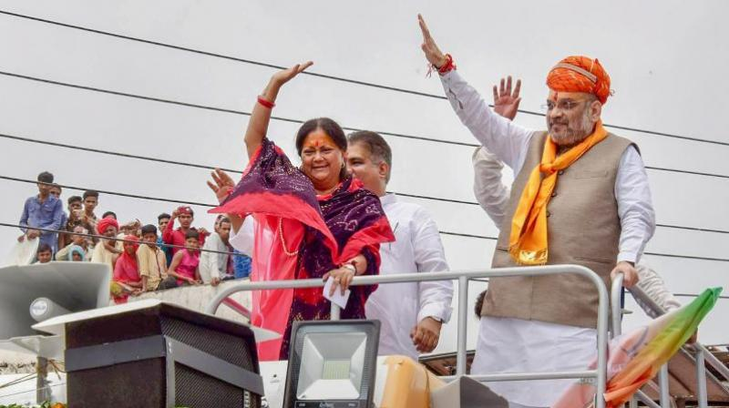 BJP President Amit Shah with Rajasthan Chief Minister Vasundhara Raje wave at a public meeting. (Photo: PTI)
