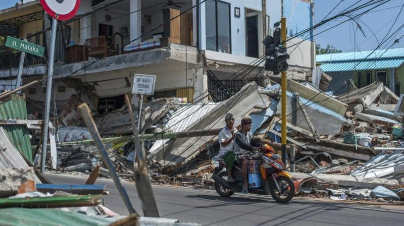 Motorists ride past buildings ruined by the quakes in Pamenang, Lombok Island, Indonesia on Friday.(Photo: AP)