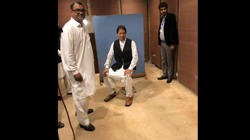 One of the National Assembly employees took off his black waistcoat and gave it to Imran Khan. The employee also helped him wear the waistcoat. (Photo: Twitter | @PTIofficial)