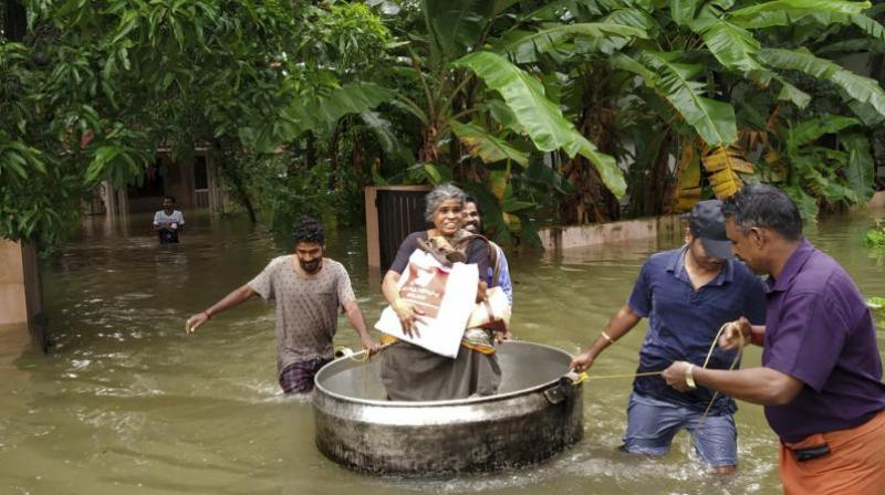 An elderly woman is rescued in a cooking utensil after her home was flooded in Thrissur, Kerala. (Photo: File)