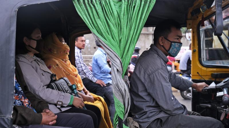 Passengers wear face masks as a precaution against the Covid-19 virus travel in an autorickshaw in Imphal, the capital of Manipur on March 20, 2020. (AP)