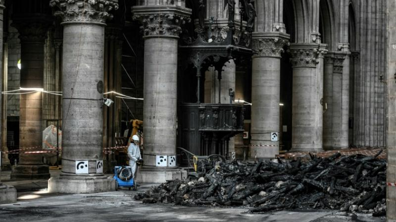 On Wednesday, instead of crowds, only a few dozen specialist workers wearing white protective overalls, hard hats and masks could be seen carrying out painstaking work to make the building safe. (Photo: AFP)