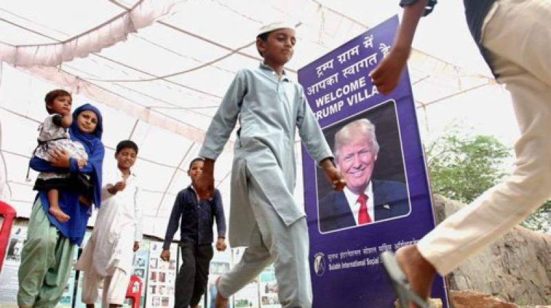 People walk past a poster of the US President Donald Trump at Maroda Village which was renamed as