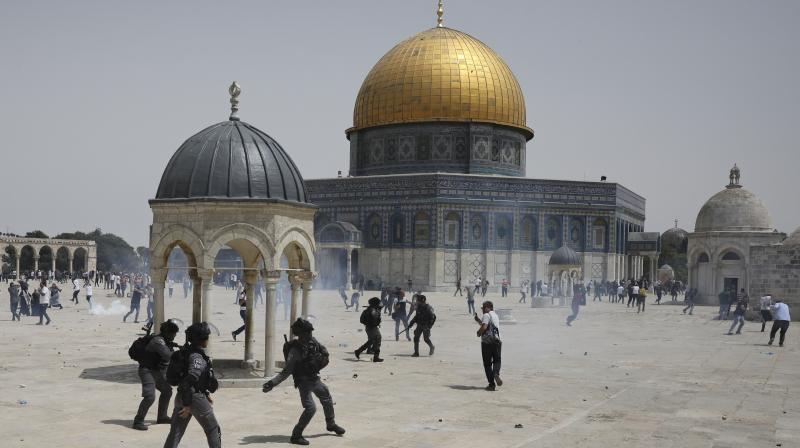 Palestinians run from sound grenades thrown by Israeli police in front of the Dome of the Rock in the al-Aqsa mosque complex in Jerusalem, Friday, May 21, 202, as a cease-fire took effect between Hamas and Israel after a 11-day war. (AP/Mahmoud Illean)