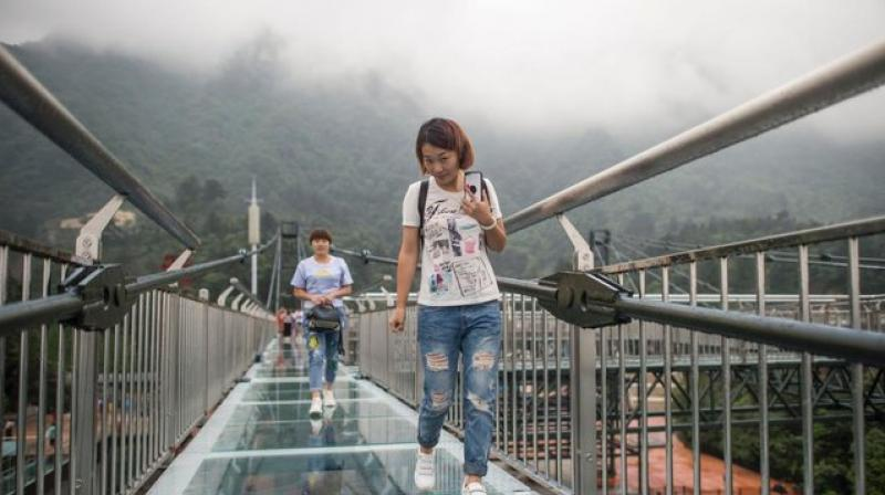 While some pause to pose for photos, others find it all a little too much to cope with, and grip the handrail with both hands as they inch along the walkway. (Photo: AFP)