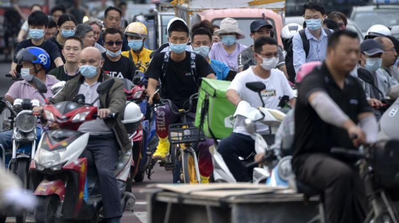 FILE - In this file photo dated Friday, July 2, 2021, people riding bicycles and scooters wait to cross an intersection during rush hour in Beijing. (Photo: AP)