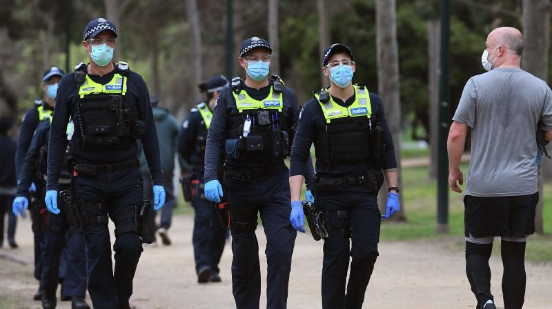 Police patrol a running track as people exercise ahead of an anti-lockdown rally in Melbourne, as the city continues to enforce strict lockdown measure to battle a second wave of COVID-19 coronavirus infections. (AFP)