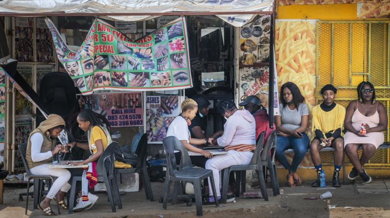 Customers have their nails done near the Baragwanath taxi rank in Soweto, South Africa, Wednesday Sept. 16, 2020. South African president Cyril Ramaphosa is scheduled to address the nation later in the day, as case numbers and death from Covid-19 hit the lowest in months. (AP)
