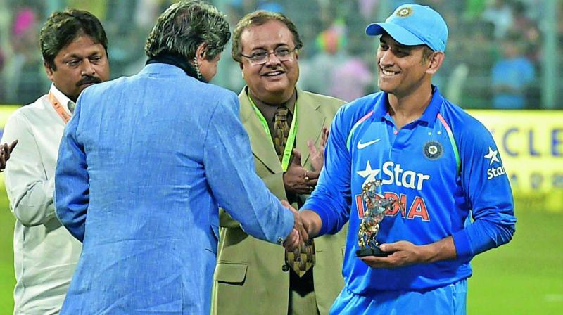 M.S. Dhoni is felicitated by former India captain Kapil Dev at the Eden Gardens.