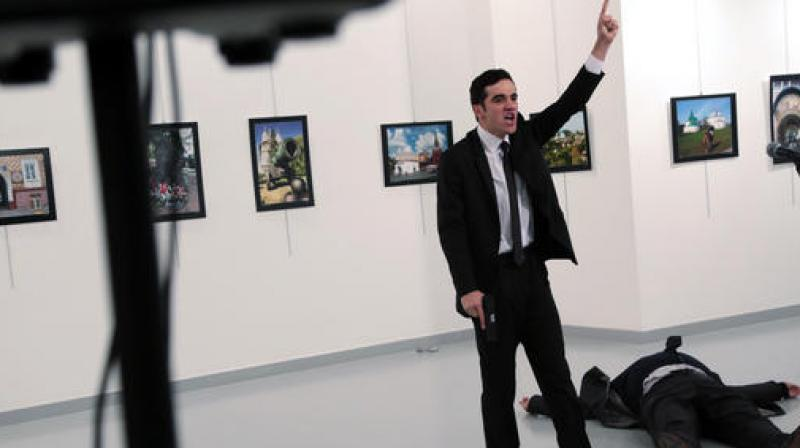A man identified as Mevlut Mert Altintas shouts after shooting Andrei Karlov, the Russian Ambassador to Turkey, at a photo gallery in Ankara, Turkey. (Photo: AP)