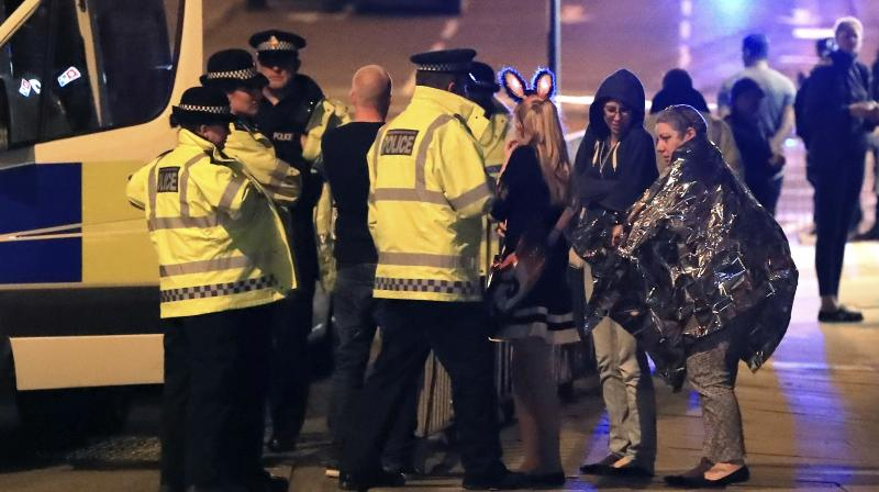 Emergency services personnel speak to people outside Manchester Arena after reports of an explosion at the venue during an Ariana Grande concert in Manchester, England. (Photo: AP)