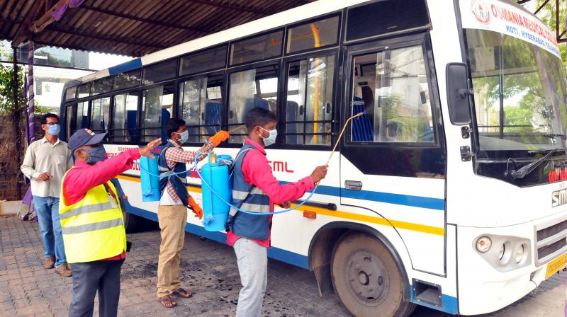 Staff sanitise a bus belonging to the Osmania Medical College in Hyderabad as it became known that several post-grad medical students of the college have become coroonavirus positive due to poor adherence of treatment protocols in the state-run hospitals in Telangana. (AA Photo: PS)