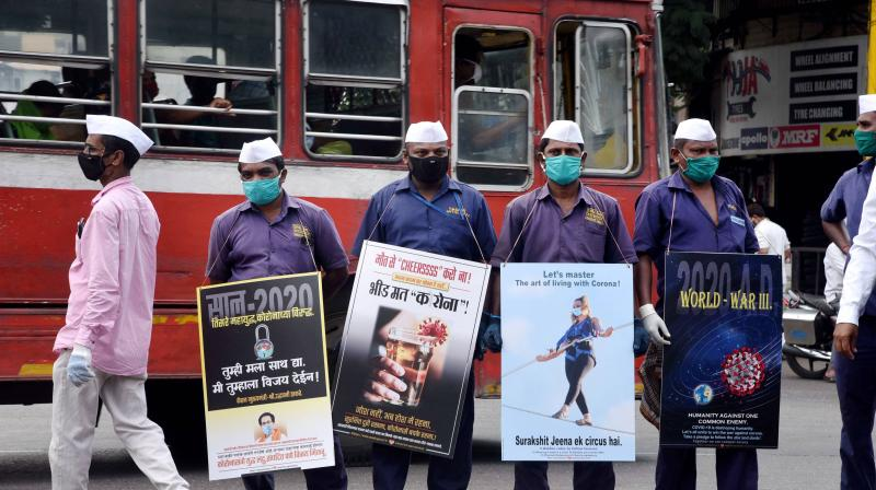 Navi Mumbai Municipal Corporation (NMMC) workers hold posters during an awareness drive against the coronavirus pandemic on the occasion of Mahatma Gandhi's 151st birth anniversary, at Turbhe in Navi Mumbai, Friday, Oct. 2, 2020. (PTI)