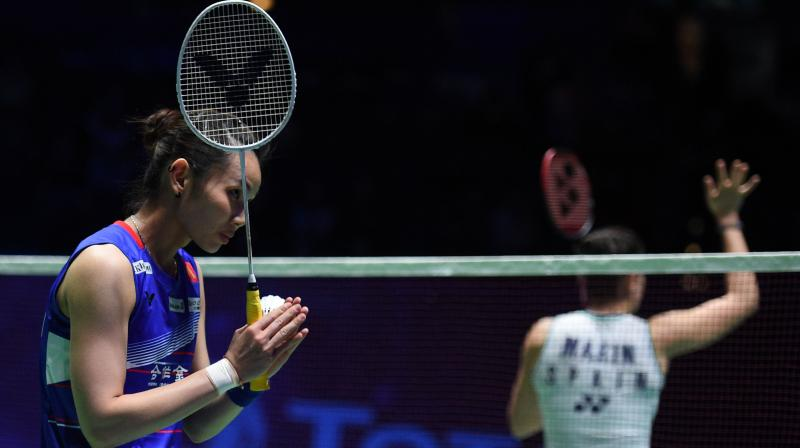 Taipei's Tai Tzu Ying celebrates after winning against Spain's Carolina Marin (back to the camera) after their semi-final at the All England Open Badminton Championships in Birmingham, central England, on Saturday. AFP Photo