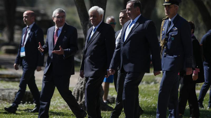 IOC President Thomas Bach (2nd left) arrives for the flame lighting ceremony at the closed Ancient Olympia site, birthplace of the ancient Olympics in southern Greece, along with Head of the Hellenic Olympic committee Spyros Kapralos and Greek President Prokopis Pavlopoulos last Wednesday. AP Photo