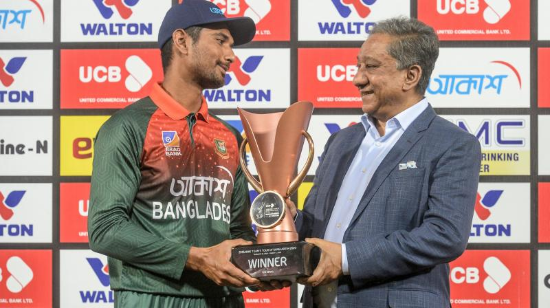 Bangladesh's team captain Mahmudullah (L) receiving the trophy from Bangladesh Cricket Board president Nazmul Hasan Papon after winning the second Twenty20 international of a two-match series against Zimbabwe at the Sher-e-Bangla National Cricket Stadium in Dhaka on March 11, 2020. AFP Photo