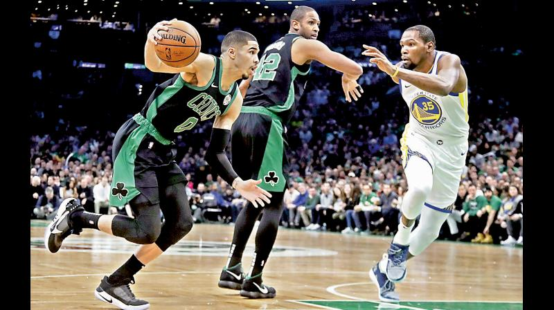 Brooklyn Nets forward Kevin Durant (R) tries to stop Boston Celtics forward Jayson Tatum even as Celtics center Al Horford provides the screen. AP Photo